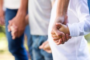 Family holding hands showing how Benefits of parental cooperation during divorce.