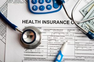 Health insurance application form with banknote and stethoscope