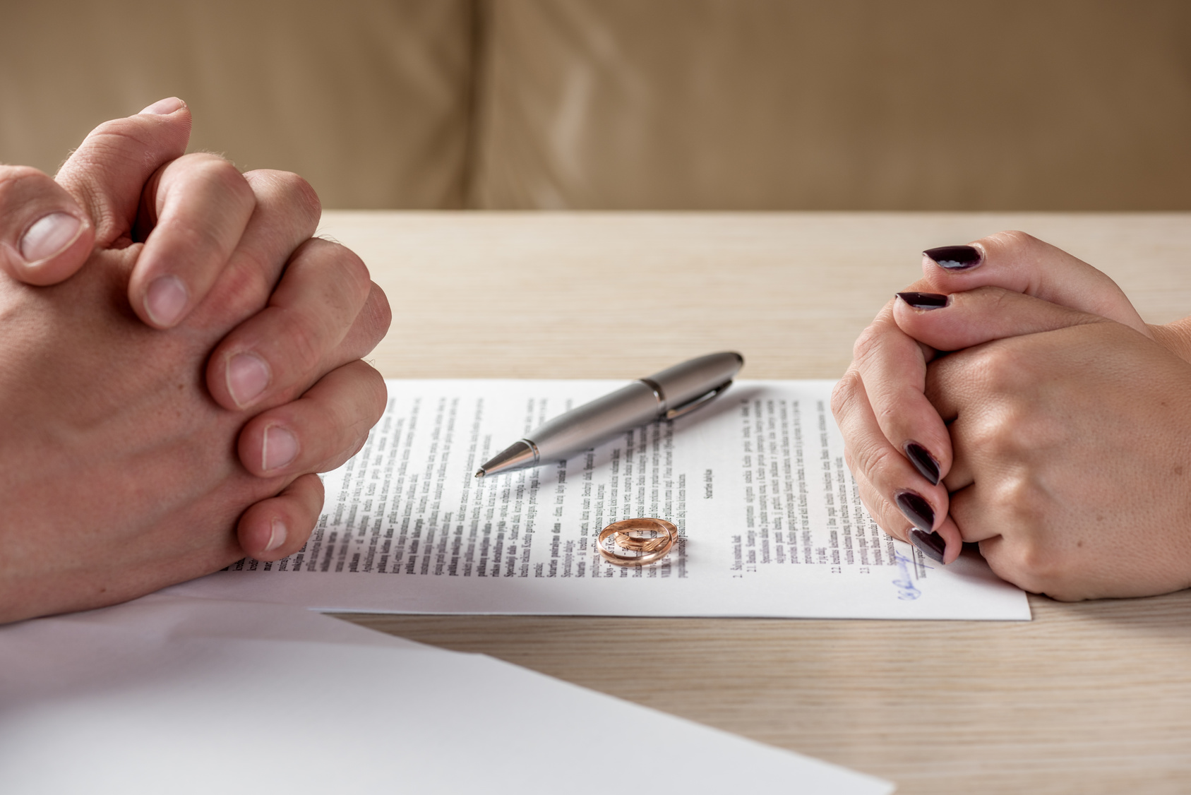 Wife and husband signing divorce documents with help from divorce lawyers dayton