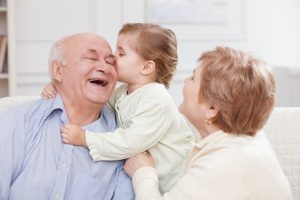 Girl is kissing her grandfather with joy. They are sitting on sofa and laughing Grandparents' Visitation Rights in Ohio