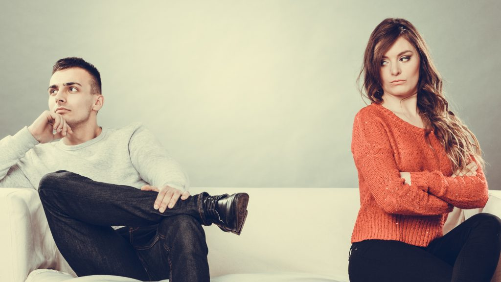 Woman and man sitting on couch in disagreement of their divorce in Fairborn