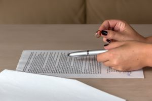 hands of wife signing divorce papers for a top xenia divorce attorney