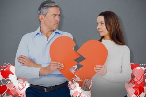Older couple hold half of a broken paper heart and if you are older and want to divorce contact an accomplished Dayton divorce attorney.