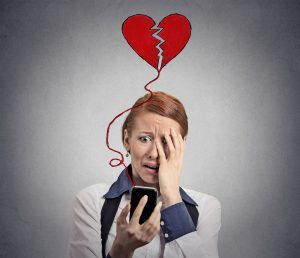 Divorcing woman looking at social media and feeling betrayed, and if you are about to divorce contact a seasoned Dayton divorce lawyer