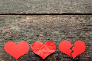 Paper red hearts on grey wooden table and if you are thinking about separation or divorce, you will find an acclaimed family law attorney in Dayton.
